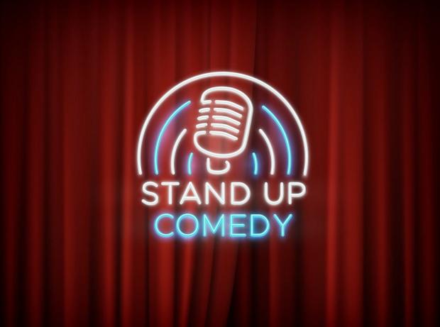 ο κωμικός στέκεται όρθιος μπροστά στο κοινό κατά τη διάρκεια της παράστασης
