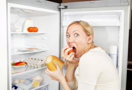 γυναίκα τρώει λαίμαργα μπροστά στο ψυγείο